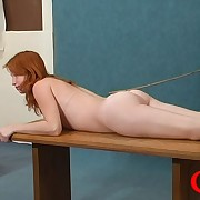 Red-haired nymph lying primarily the table yon her gluteus maximus spanked