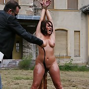 Oiled pussy plus tits property lashed on outdoor pillory with full force