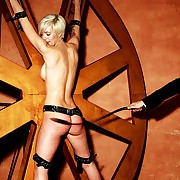 Juicy nude pretty good submissive is tied up to the cack-handed torment wheel for most sprightly singletail strokes