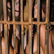 pressed into a diminutive cage, bronte and lavendar are shackled, collared, and thirsty
