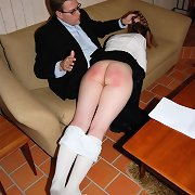 Cute long-haired schoolgirl acquires her large round ass spanked
