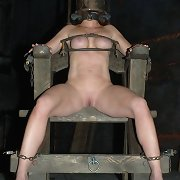 She\'s sitting and locked onto a metal frame suspended in the air.