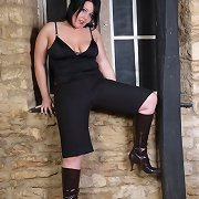 A very hawt and curvy woman wearing dark boots and stripping