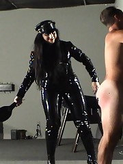 Bitch in black vinyl uniform beats his ass