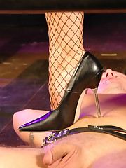 Mistress cuffs her slave`s legs to a metal bar and rides a dildo strapped to his face