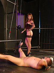 Mistress cuffs male slave to a metal bar, lifts him up and fucks his ass in upside down position