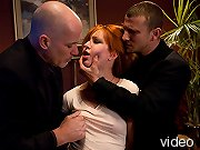 Redhead forced to her knees to service two Masters.