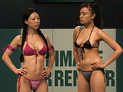 Two Asian girls in rough erotic wrestling match.