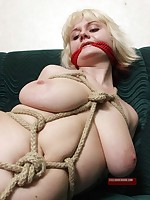 Pretty blonde gagged and bound with rope on green couch