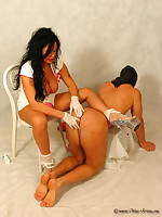 Dominatrix nurse administers an enema to male patient