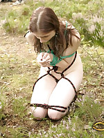 Submissive girl bound with rope and abandoned in meadow