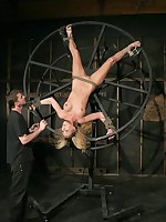 Slavegirl suspended, tied to a wheel