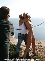 A woman is held in place for some serious beachside whipping