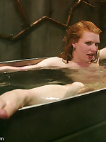 Redhead is suspended over a tub of water.