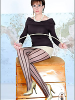 Stern Domme in striped stockings teases camera