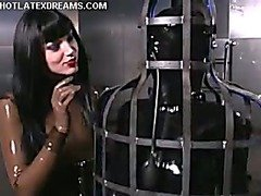 Submissive in latex trapped in upright cage.
