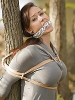 Pretty girl tied in rope to a tree