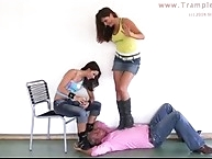 Two smoking mistress trample on dressed slave