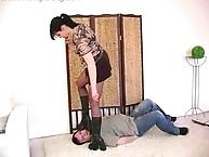 Brunette mistress stands on slaves face