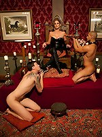 Hot dominatrix uses two slaves in chastity for her pleasure, milking one's prostate with her fist until he starts dripping out his belt.