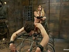 Dominatrix in leather clothes having humiliating fun with slave