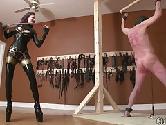 Latex brunette was spanking her roped slave hard