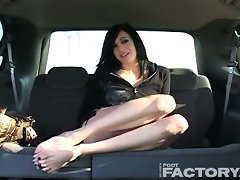 The girl shows her pretty feet in the car