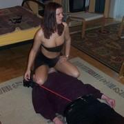Misrtess in black skirt sat on slave