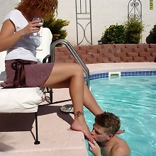 Slaves worshipping mistress` feet near the pool