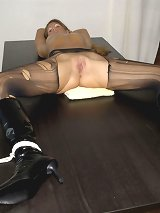 A blonde in ripped pantyhose was tied on the table