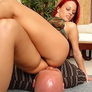 The cool redhead sits on slave` face