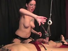 Mistress seems pleased with herself as she stretches her slave\'s balls and nipples and tortures him